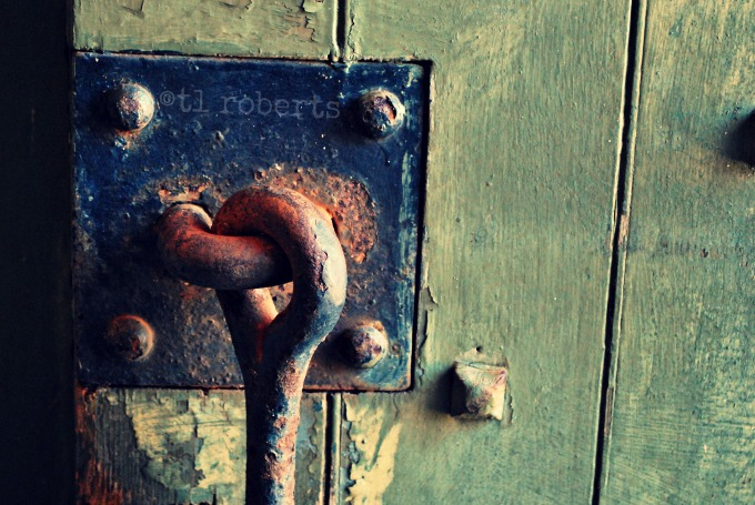 rusted metal latch on a wooden door