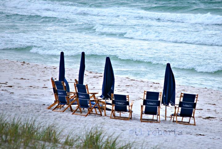 blue beach chairs on white sand