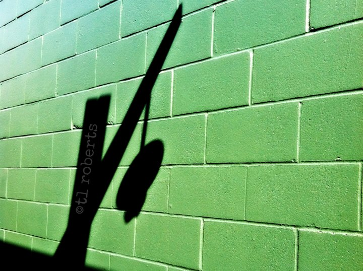 street lamp shadow on a green wall