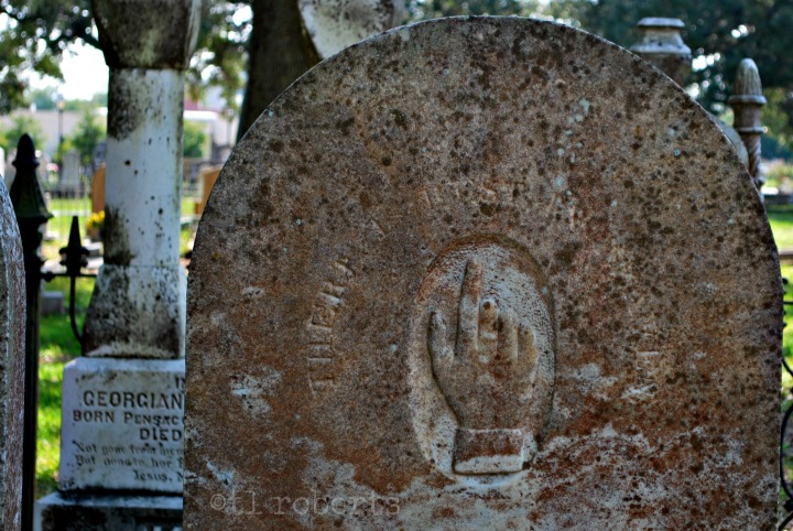 gravestone with pointing finger