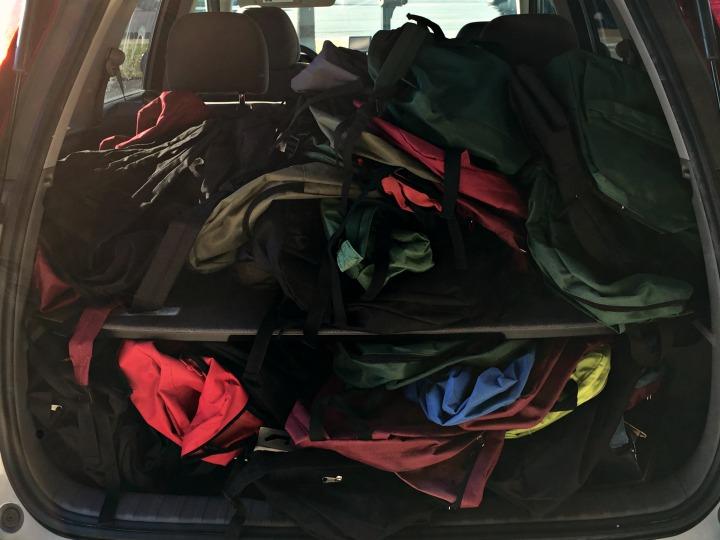 car full of empty backpacks