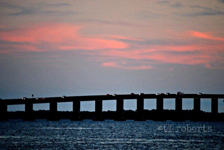 car lights on bridge at sunset