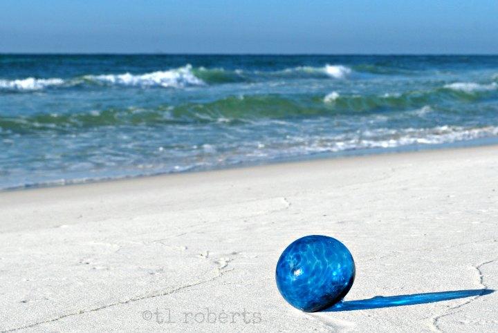 blue glass Christmas ornament on a white, sand beach