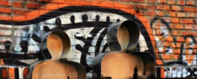 metal people sculpture with graffiti