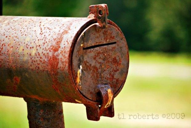 rusty round metal mailbox
