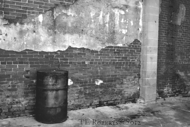 black and white shot of a metal trashcan against a brick wall