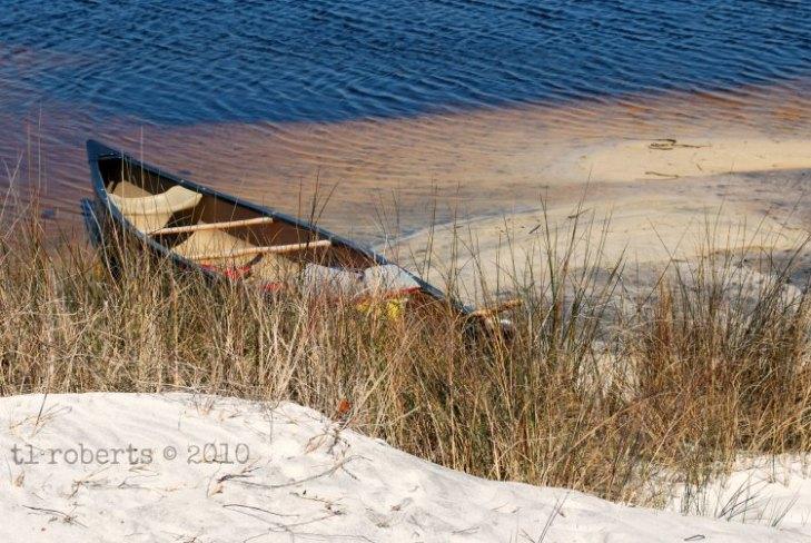 grounded canoe on sandy bank